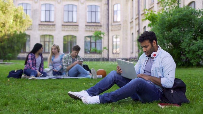Student för blandat lopp som använder bärbara datorn som direktanslutet sitter på gräs på universitetsområde, utbildning royaltyfria bilder
