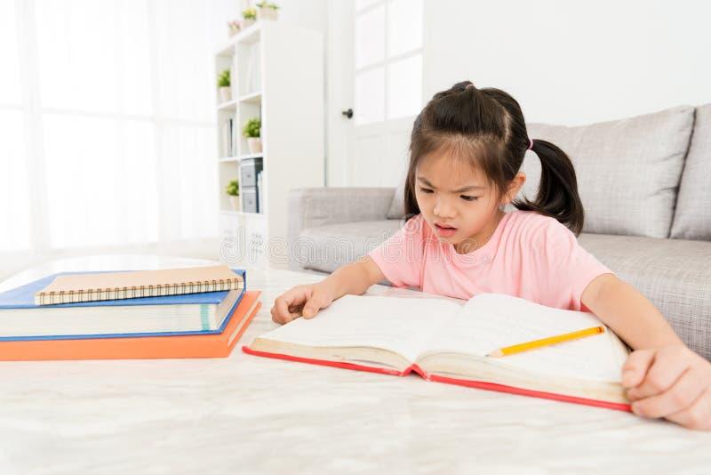 Student för liten unge som ser skolaläroboken fotografering för bildbyråer