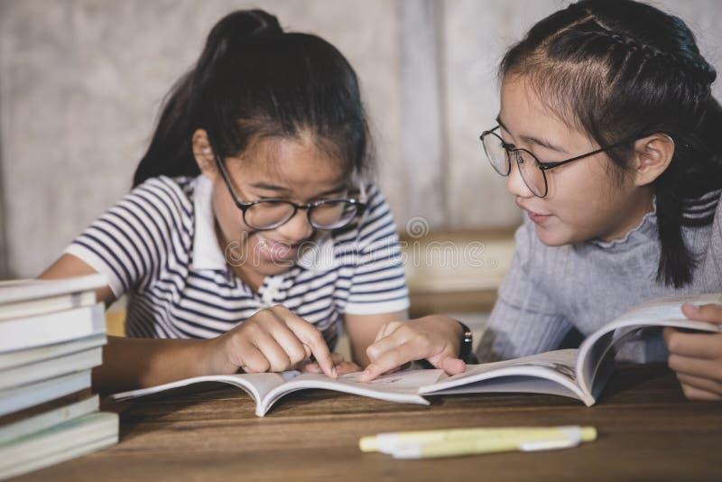 Student för två asiat som läser en skolbok med lyckasinnesrörelse fotografering för bildbyråer