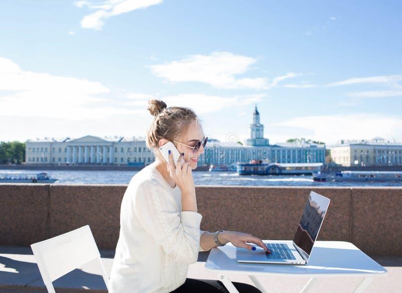 Student för ung kvinna som talar på mobiltelefonen under arbete på bärbar datordatoren som sitter nära invallningfloden arkivbild