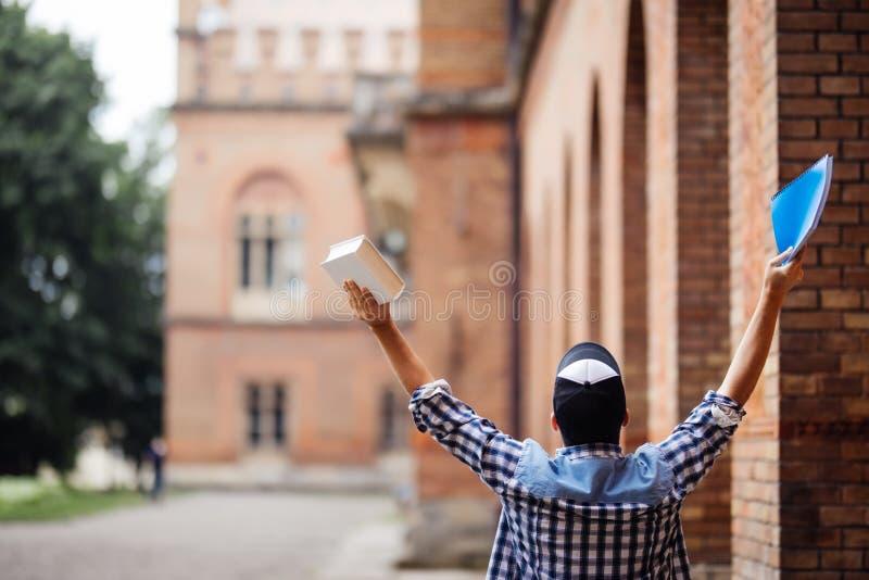 Student för ung man med lyftta händer av framgång framme av Uni universitetsområdet Happuseger för ung man av passerandeexamen St arkivfoto