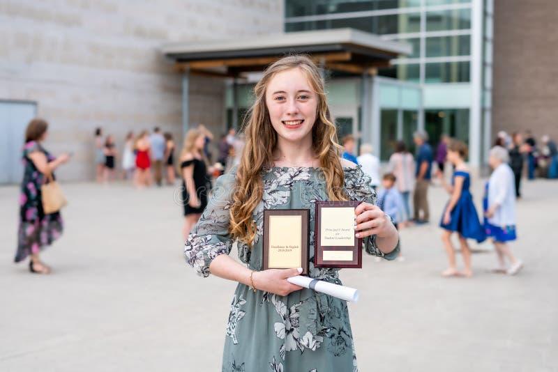 Student för ung tonårig flicka som/mellanstadiumframme står av skola med utmärkelser och diplomet efter skolaavläggande av examen arkivfoto