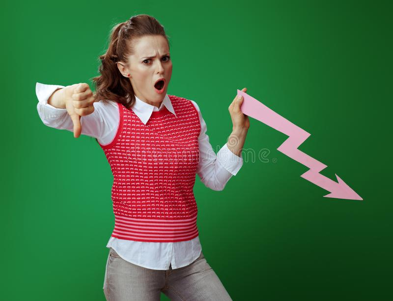 Student with falling down graphics arrow showing thumbs down. Shocked healthy student in grey jeans and pink sleeveless shirt with falling down graphics arrow royalty free stock photography