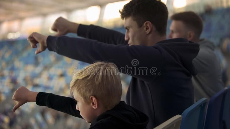 Student fans and little boy booing sport game at stadium, watching junior match. Stock photo royalty free stock images