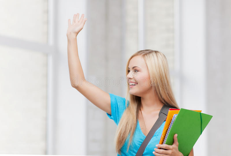 Student with folders. Picture of smiling student with folders waving her hand royalty free stock photo