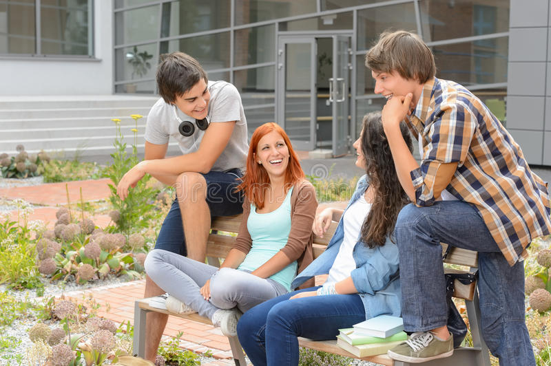 Student friends sitting outside campus laughing stock photos