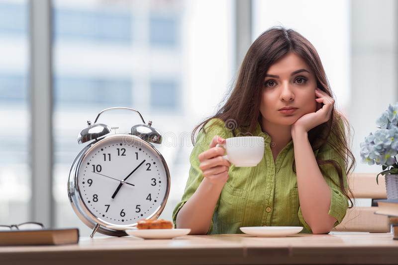 The student with gian alarm clock preparing for exams stock photo