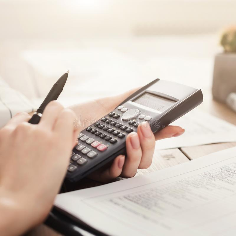Student girl calculating with calculator and writing notes stock images
