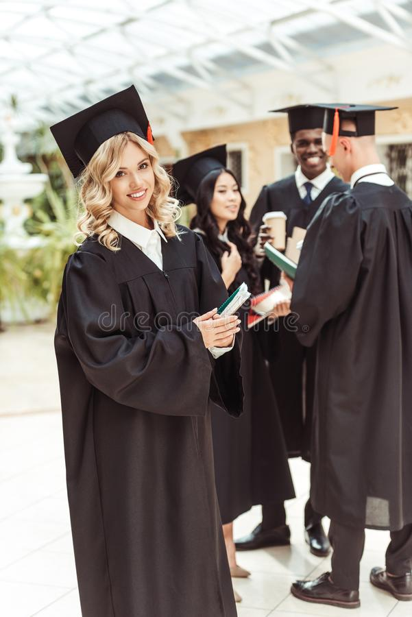 Attractive young student girl in graduation costume with multiethnic group of students. On background stock photography