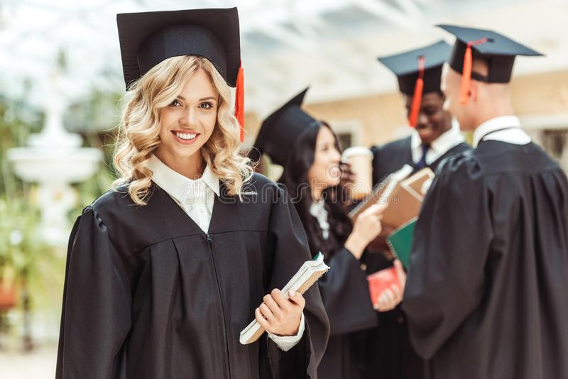 Student girl in graduation costume. Beautiful young student girl in graduation costume with multiethnic group of students on background royalty free stock images