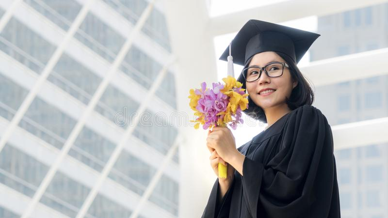 Student girl in graduation with flower bouquet. The student girl in graduation with flower bouquet stock photo
