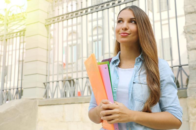 Student girl holding folders outdoor looking to the side the copy space.  stock images