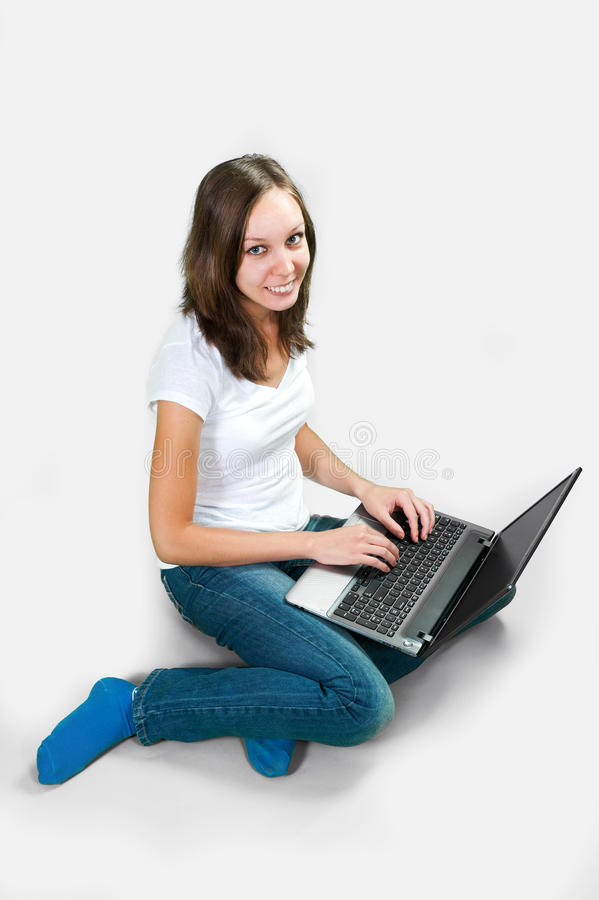 Student girl with laptop computer on gray background stock photography