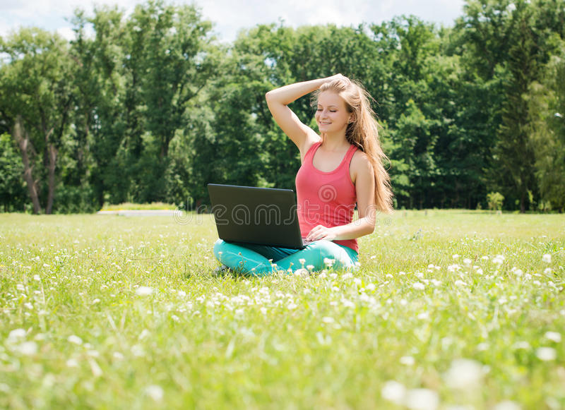 Student girl with laptop outdoors. College or university student young woman in summer park smiling happy. royalty free stock photos
