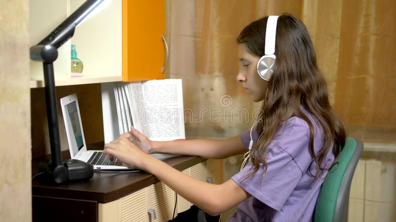Student girl learning on line with a white laptop sitting at a table in her teen room. in evening time royalty free stock photography