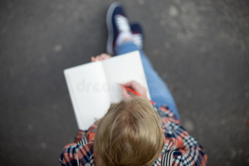 Student girl making notes in a copybook stock image