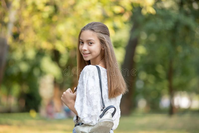 Student girl outside in summer park smiling happy. female college or university student. young woman model wearing school bag royalty free stock photo