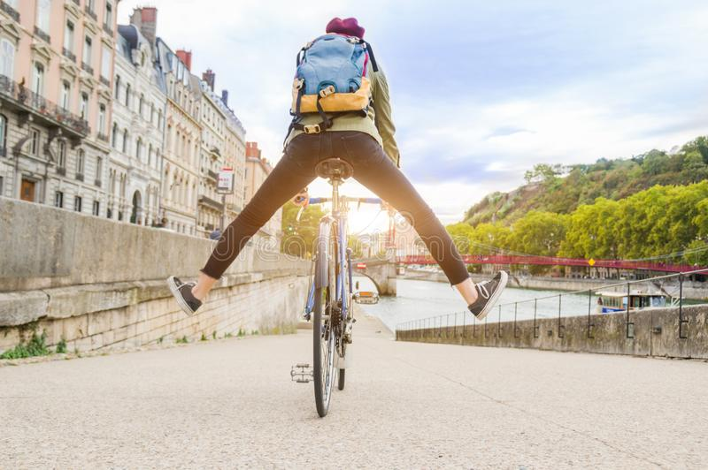 Young active woman riding a bicycle going down the road in the city. Student girl riding a bicycle going down the road near the water and having fun in the city stock photo