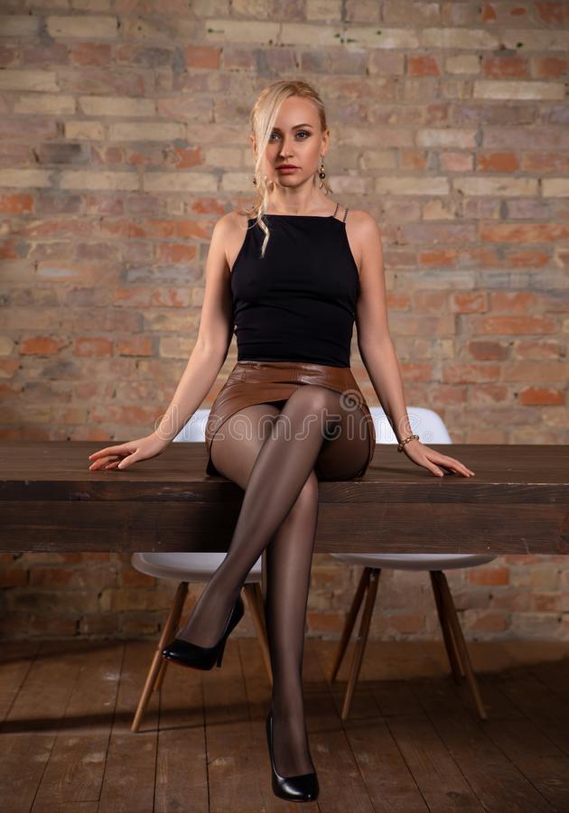 Student girl sitting on the library table in pantyhose royalty free stock photos