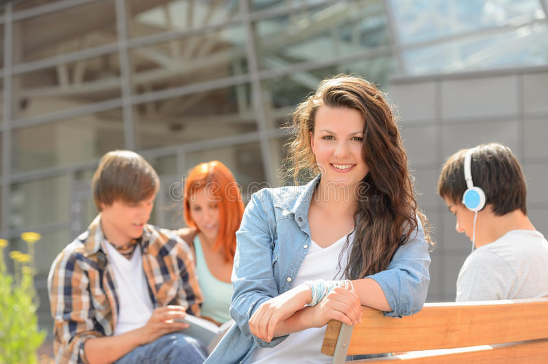 Student girl sitting outside campus with friends royalty free stock image