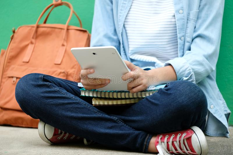 Student girl sitting and using digital tablet, online education, adult learning concept stock photography