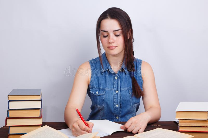 Student girl studying, reading textbook and noticing material to. Copybook. Portrait of diligent young beautiful woman writing precis. Education, learning stock image