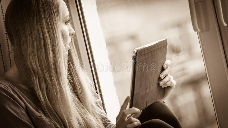 Student girl with tablet sitting on windowsill royalty free stock photo