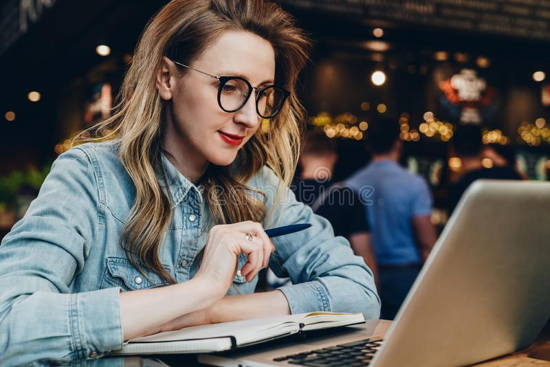 Student girl in trendy glasses sits in cafe in front of computer, laptop watches educational webinar. Online education. royalty free stock image