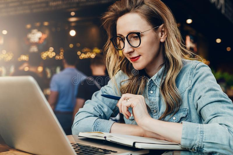 Student girl in trendy glasses sits in cafe in front of computer, laptop watches educational webinar. Online education. stock images