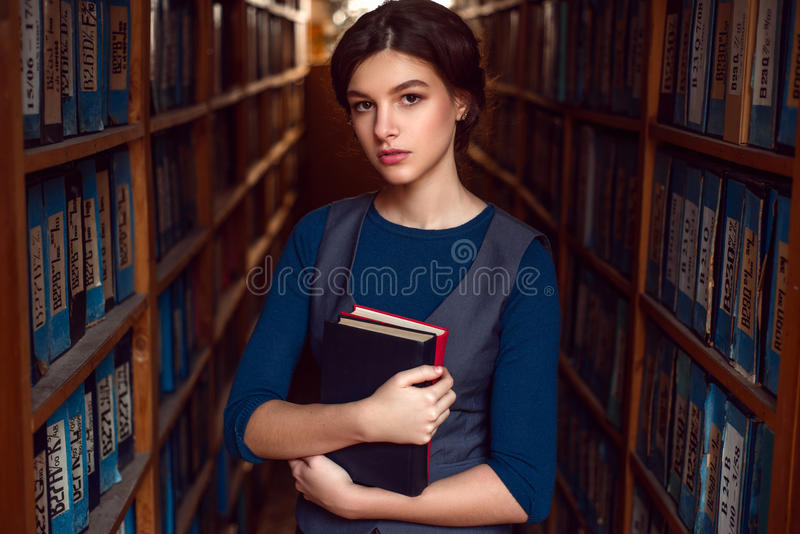 Student girl or woman with books in library. Student girl or woman with books between bookshelves in library royalty free stock photos