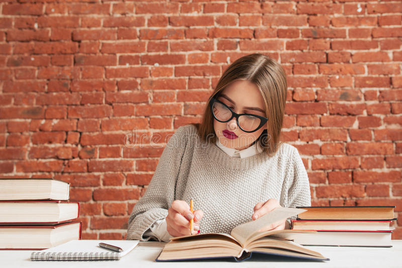 Student girl writing conspect free space. Young beautiful woman studying, reading textbook and noticing material to copybook. Education, learning, preparing royalty free stock image