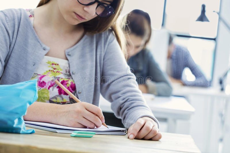 Student girl writing test in classroom stock images