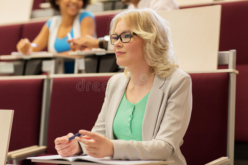 Student girl writing to notebook in lecture hall stock images