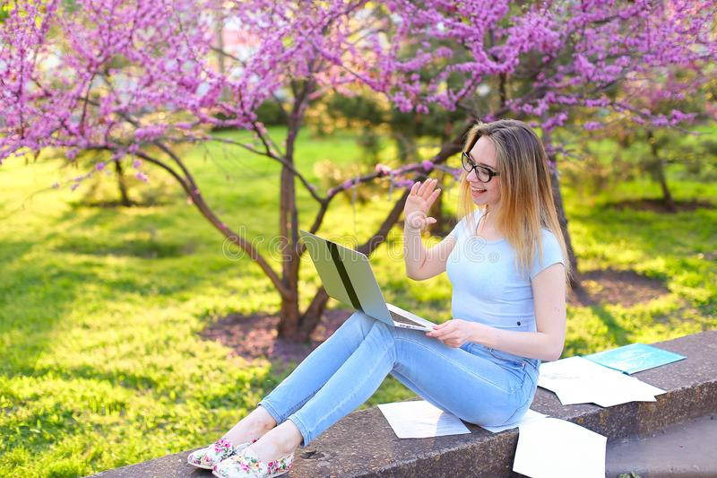 Student in glasses making video call by laptop in spring park. stock photo