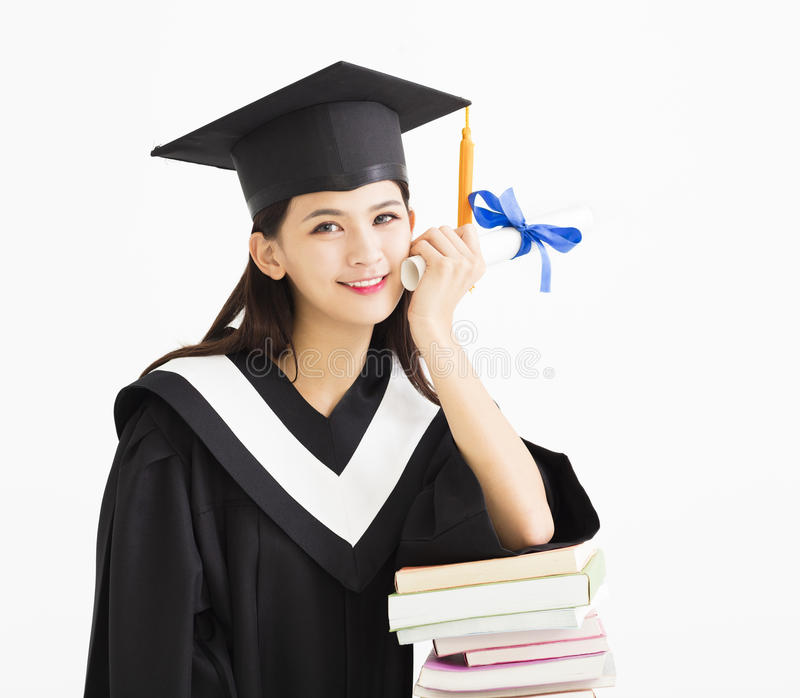 Student in graduation cap with stack of books royalty free stock photo