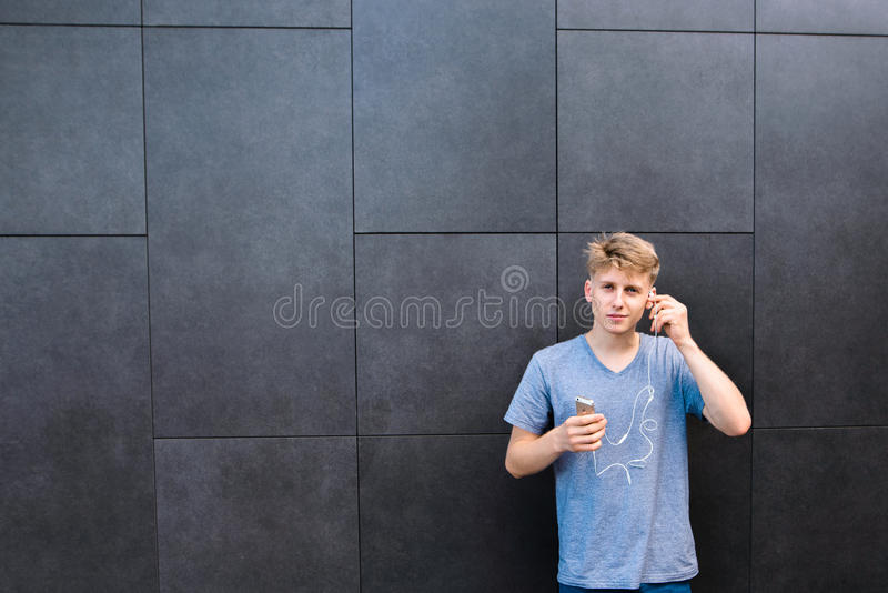 Student in a gray t-shirt stands with a phone and hands on the background of wall and inserts a headphone into the ear. royalty free stock photos