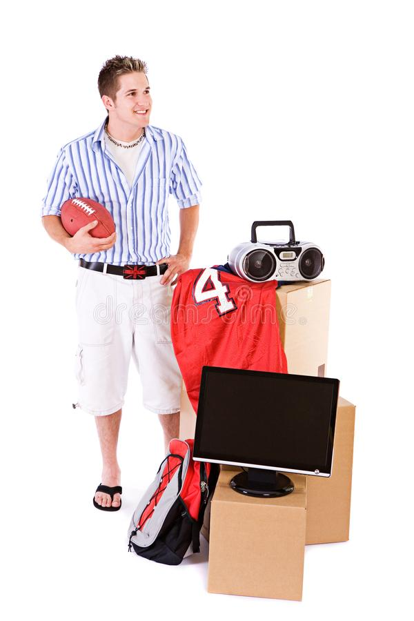 Student: Guy Holding Football With Stack Of Dorm Room Stuff royalty free stock images