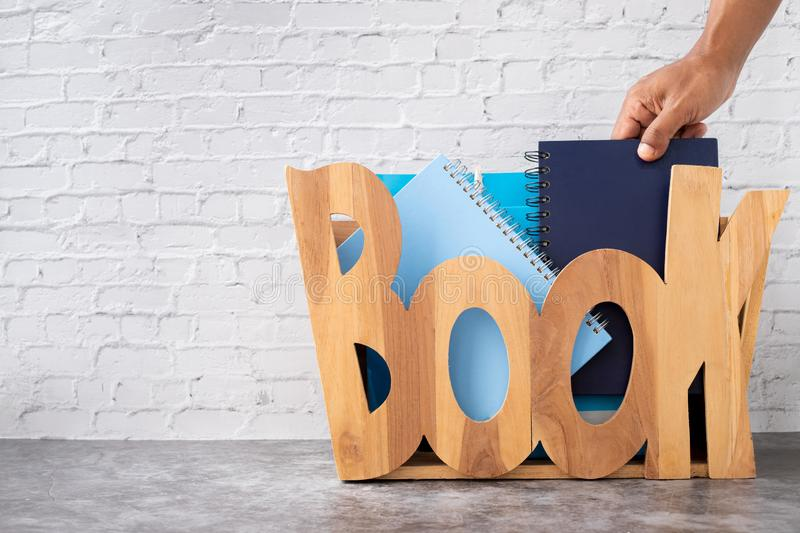 Student hand choosing and picking off book from wooden box on brick wall texture background royalty free stock photography