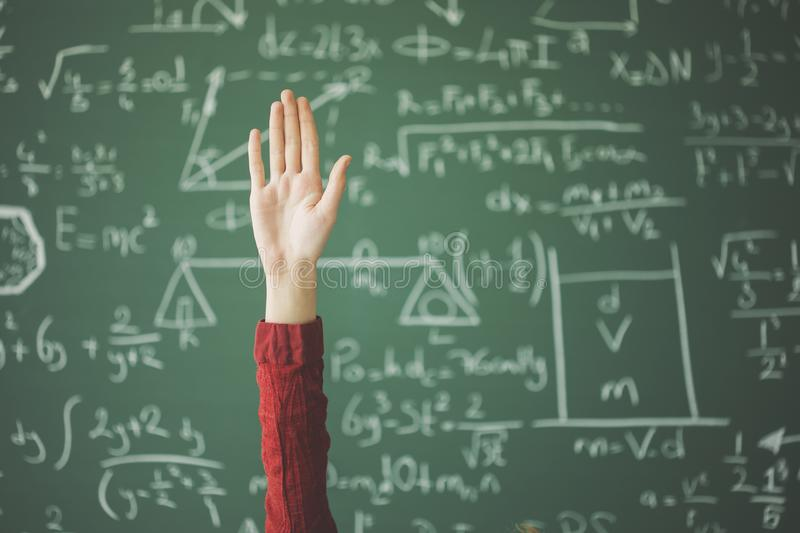 Student hand up behind green chalk board royalty free stock photo