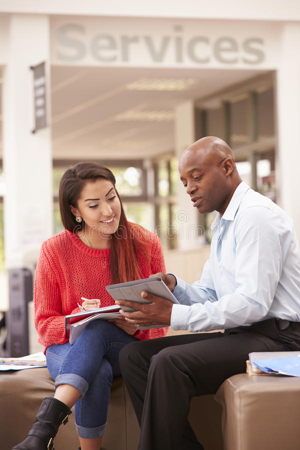 Student-Having Meeting With-Tutor To Discuss Work stockbild