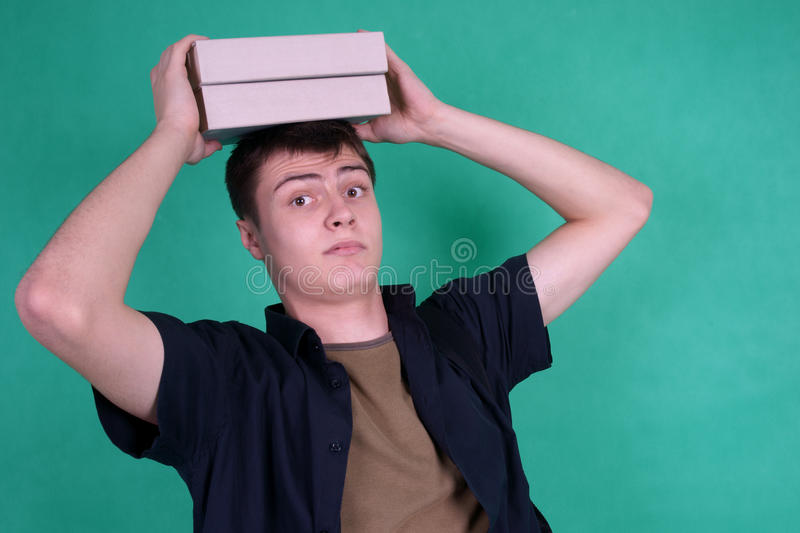 Download Student With Heavy Books On His Head Stock Photo - Image: 12277360