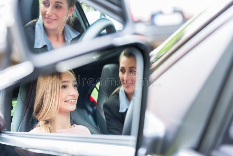 Student in het drijven van school bij het wiel van een auto met haar instructeur royalty-vrije stock afbeeldingen