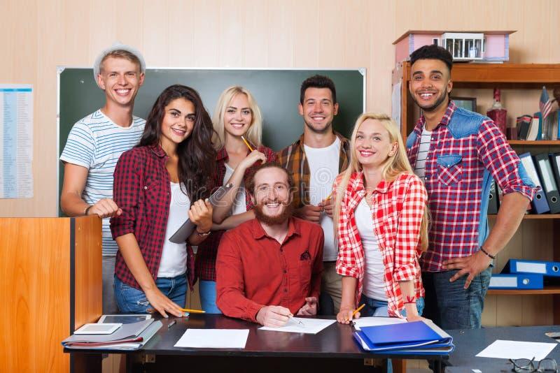 Student High School Group med professorn Sitting At Desk som ler klassrumet för ungdomaruniversitet royaltyfria bilder