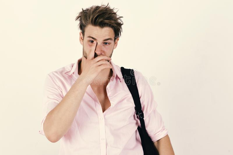 Student or highschooler goes to school or university. Man rubs his eye and wears backpack isolated on white background. Guy in pink shirt with rucksack on stock image