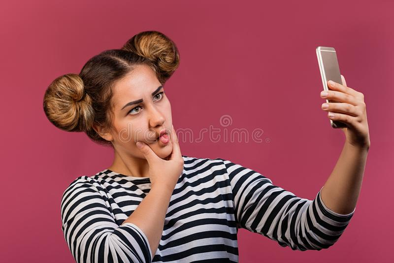 Student hipster girl with funny hairstyle and face expression making selfie photo, isolated stock image