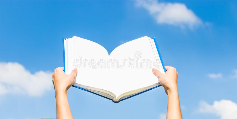 Student hold the book on her head in park stock photo