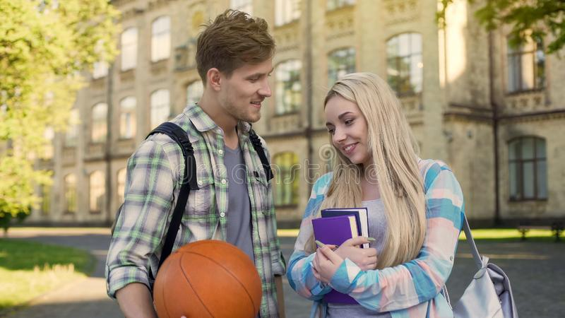 Student holding ball, flirting with pretty girl near university, asking for date stock photos