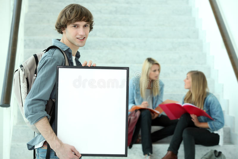 Student holding blank poster. Student at university holding a blank poster royalty free stock image