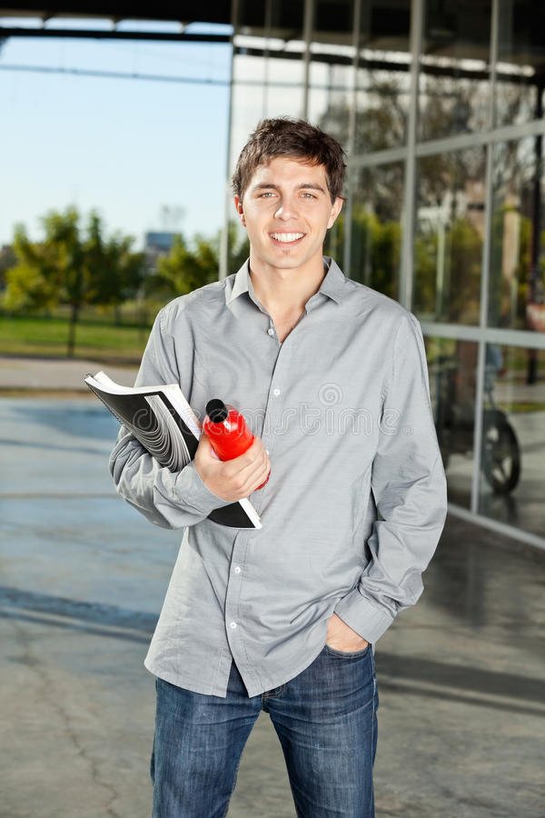 Student Holding Book And Juice Bottle On Campus royalty-vrije stock afbeelding