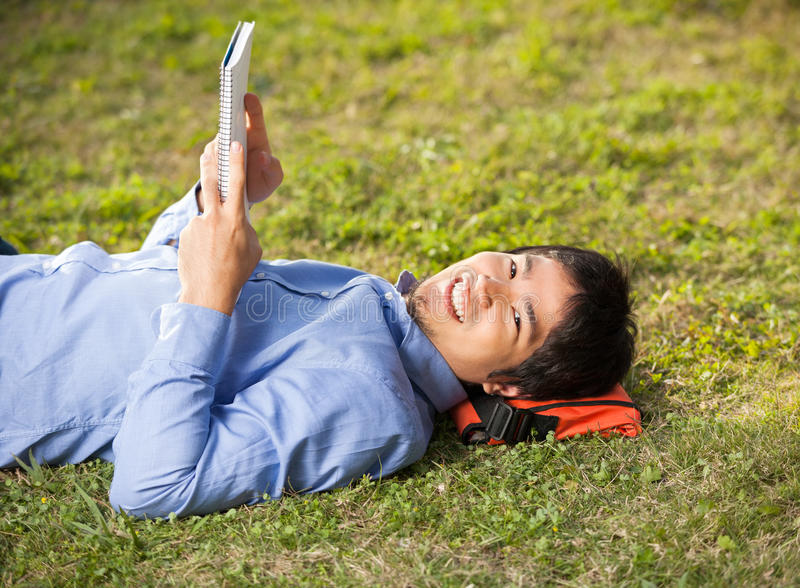 Student Holding Book While Lying On Grass At stock photography